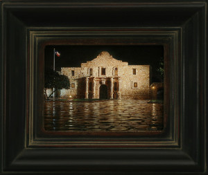"""Alamo Night"" by Rod Chase, is a beautiful night scene. The Alamo stands strong and alone in the dark, no people, and no city lights. Hill chose a traditional profile...a dark brown finish with a heavily antiqued gold lip edge, giving age to the frame. Hill wants the viewer to go right to the center of the painting, having nothing distracting the viewer's eyes from the painting. The color choice and antiquing give the frame an aged appearance."