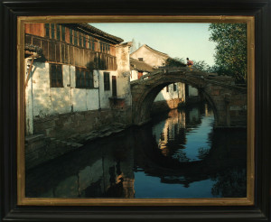 """Morning in the Water Valley"" by Wang, depicts an area of China. The frame is slightly scooped with a simple profile, black with red rubbed finish. Carved into the composition gold lip area are soft rounded edges, giving an Asian feel to the frame."