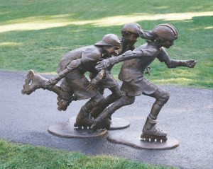 """ Catch Me If You Can "" - Life Size- ""The sculpture captures the image of members of CSU roller blading team whizzing past my house on the bike trail all summer when I lived in Fort Collins, CO. Their mobility and independence impressed me. I looked intensely as they sped by me, soaking up all I could about them….their shirts billowing in the wind. As I ran back into the studio, I worked quickly each day trying to capture what I had seen in my small maquette. The sculpture is designed as a diagonal triangle from  every vantage point to express the bladers' action. It is such an exciting sport that I went to a sports store's promotion to try it for myself and came home with a pair of roller blades. """